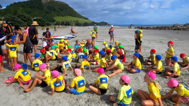 Wearing bathing caps sorted by color for each age group, the kids prepare for 2 hours of surf lifesaving class