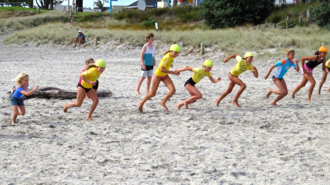 The girls run sprints in the sand