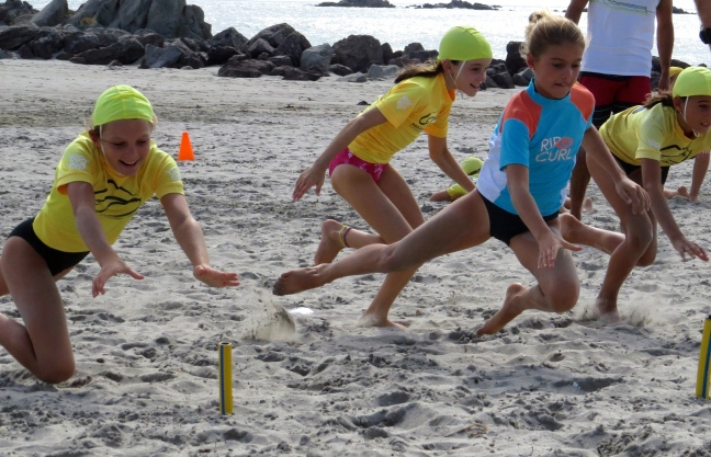 Schuyler practices her sand dive, reaching for that yellow baton