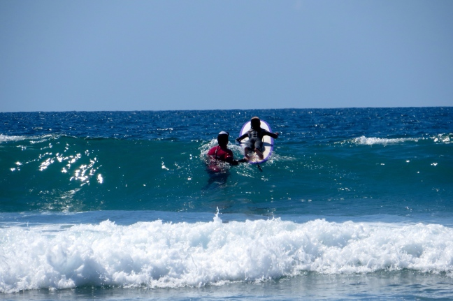 Schuyler and her instructor, Bjorn, head into the waves
