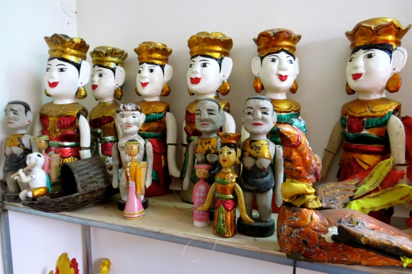 Hand-carved water puppets line the shelves of Phan Liem's home