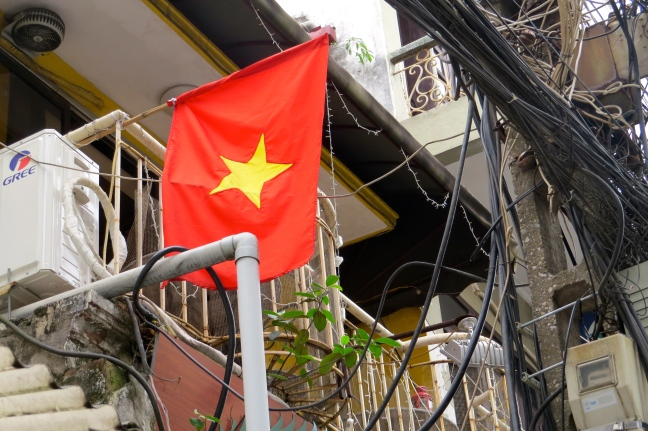 The Vietnamese flag, flanked by thousands of uncovered electrical wire that ropes through the streets