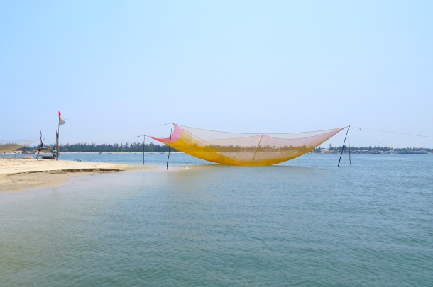 large fishing net, poised to be lowered into the sea at night
