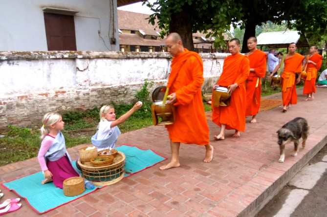 Zoe offers a handful of rice to each monk