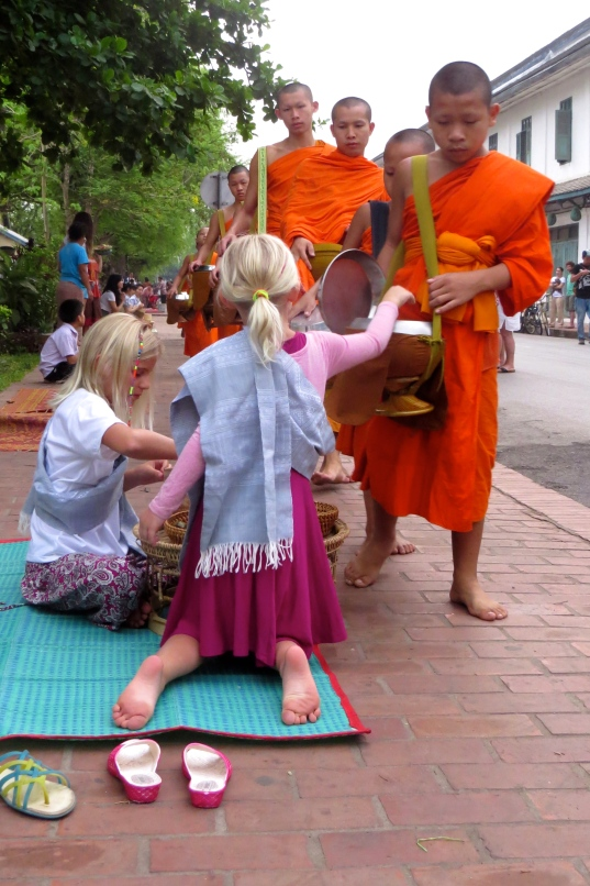 Thayer hands some food to one of the younger monks in the line