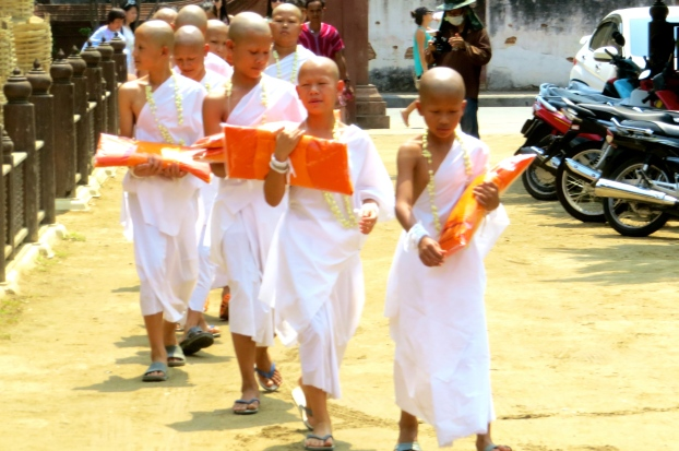 Then the boys process to an area where they can change from their white robes to their new orange monk robes