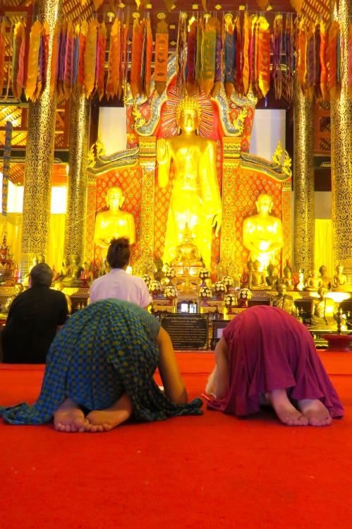 Zoe and Thayer practice their prostrations at the altar, as demonstrated by our guide
