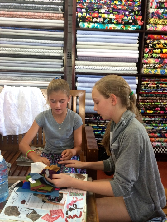 Schuyler and Haven, flanked by shelves of fabric ponder their options in the tailor shop,