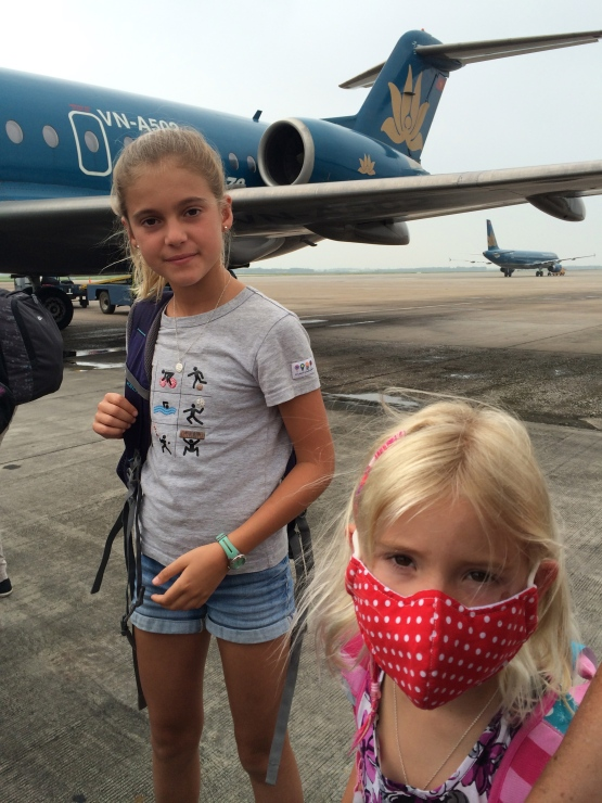 Thayer has taken to wearing masks like the locals, protecting her from fumes while motorbiking as well as the harsh sun. She boarded our flight to Laos in local style