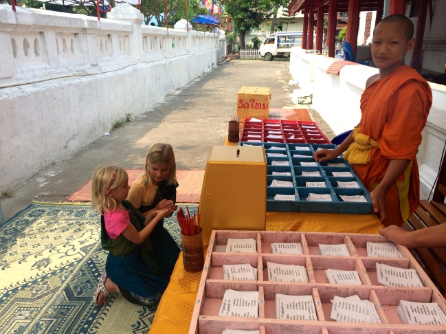 Zoe and Thayer make an offering and receive blessings from these monks