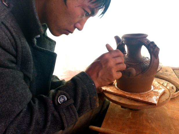 Potter working on the small details of his pot