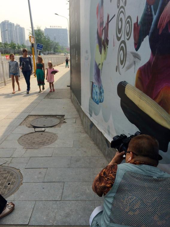 Cameraman shooting the girls and Gloria walking toward him, preparing for the interview