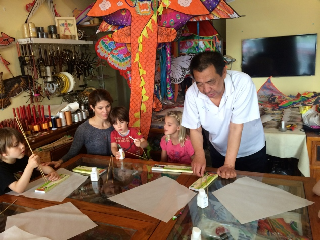 The kite maker demonstrates how to get started