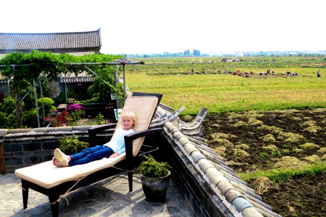 Thayer lounges on the roof deck, looking over some garlic fields