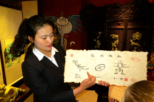 A museum guide explains some Naxi hieroglyphs before we take turns trying to draw them
