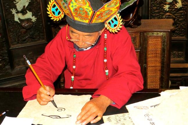 Naxi Shaman, demonstrating the art of Naxi writing at the museum