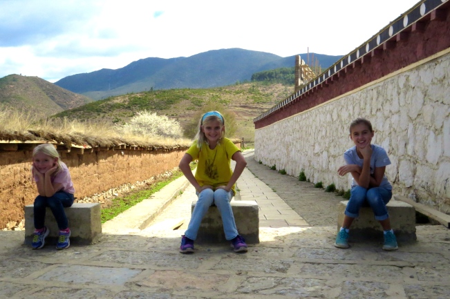 The girls stop to rest and catch their breath while climbing up to the nearby stupa