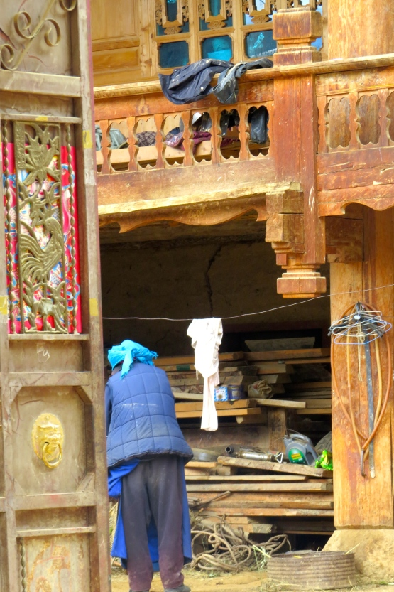 Peeking through the outer gates, we see a Tibetan woman doing some washing in her courtyard