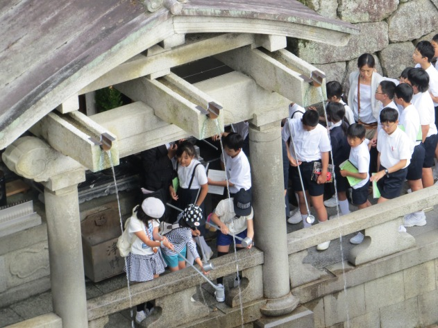 Looking down from the Temple balcony, schoolchildren collect and drink water from a waterfall known to bring luck and long life to those who drink from it
