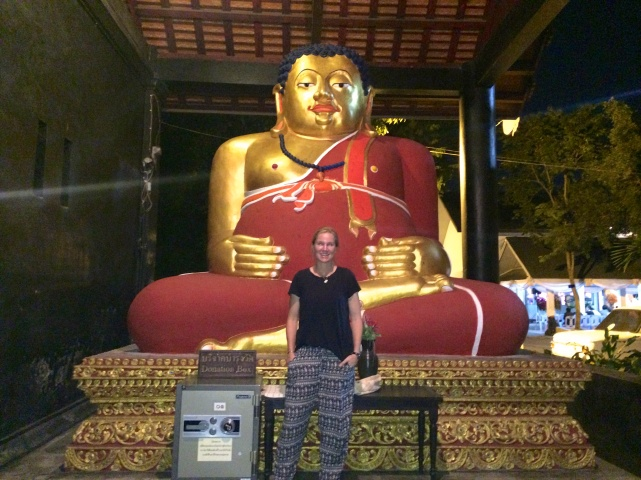 Exploring the temples at night is a much cooler option - Blair poses in front of a giant happy Buddha
