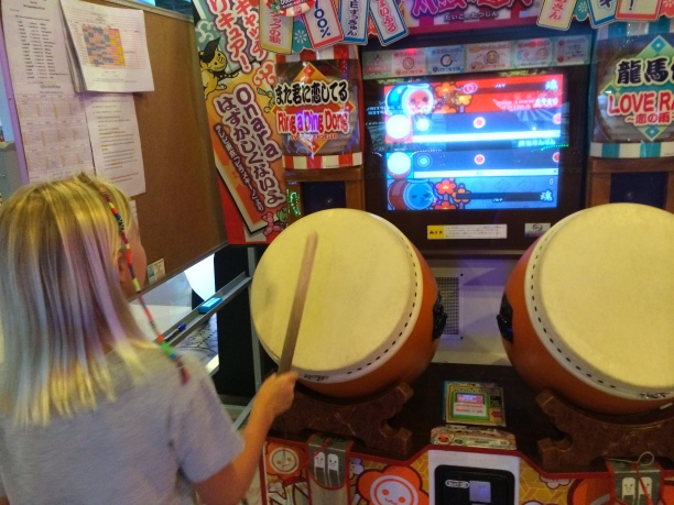 Zoe plays a Thai game like guitar hero, only with drumming