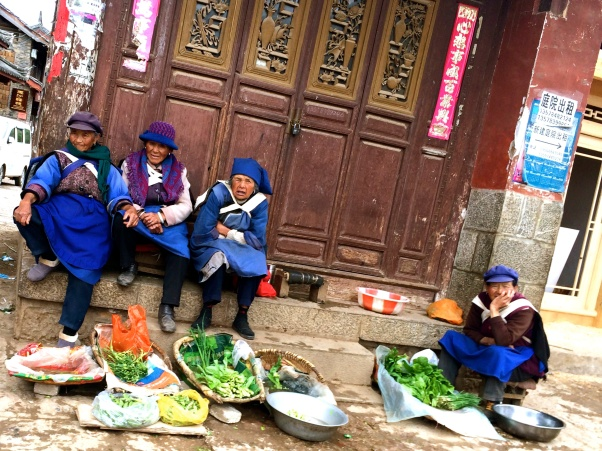 Elderly Naxi women relax in the town square