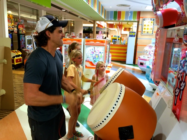 Thayer and Zoe, matching drumming expressions, compete for percussion prowess in an arcade